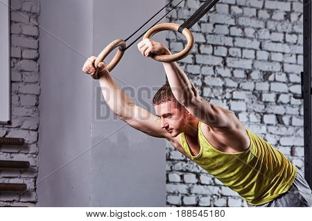 Young athlete man in the sportwear pulling up on gymnastic rings against brick wall in the cross fit gym. Portrait of the sportsman in the yellow t-shirt. Body and muscle, power and energy. Healthy lifestyle.