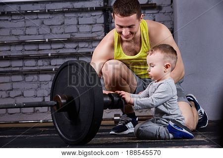Young sporty father showing dumbbells for his little son and smiling against brick wall in the cross fit gym. Father and son in the sportwear and sportive shoes. Happy family. Rearing children in the healthy lifestyle.
