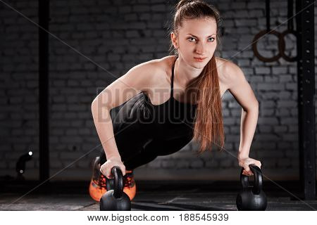 Young sporty woman in the black sportwear doing push-up exercise with dumbbell against bricl wall. Sporty woman in the t-shirt, leggins and orange sportive shoes. Close-up photo. Healthy lifestyle.