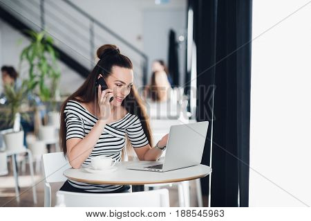 Beautiful adult woman in striped shirt is talking on the phone, holding a cup and smiling while working with a laptop in a cafe