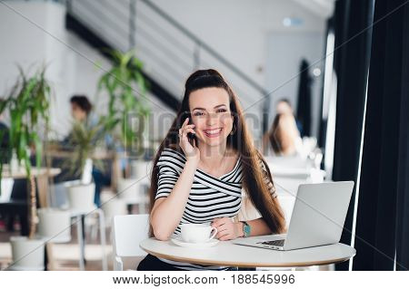 Beautiful adult woman with beautiful smile is talking on the phone and working with a laptop in a cafe while looking away