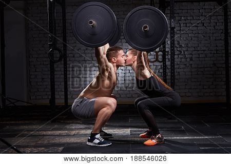 Young beautiful sportive woman and man kissing and lifting a dumbbell from squats against brick wall in the gym. Happy sportive couple. Man and woman in the sportwear and sportive shoes. Concept o f the cross fit activity in couple.