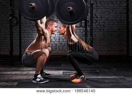 Young beautiful sportive woman and man lifting a dumbbell from squats opposite each other against brick wall in the gym. Happy sportive couple. Man and woman in the sportwear and sportive shoes. Concept o f the cross fit activity in couple.