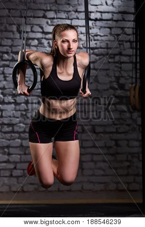 Image of beautiful young sporty woman in the black sportwear doing pull-ups exercise using gymnastic rings against brick wall at gym. Woman in the t-shirt and shorts. Healthy lifestyle.