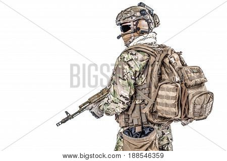 Operator of Russian special operations forces with kalashnikov assault rifle, military backpack and combat helmet. Studio shot, isolated on white background, profile view, half-turn