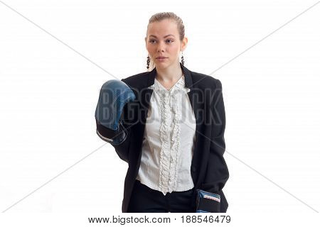 Business woman in classic uniform and boxing gloves looking aside in studio isolated on white background
