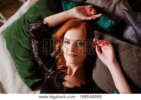 Redhead woman in black lace peignoir on the bed in her bedroom among velvet pillows resting. Sensual boudoir portrait.Sleeping beauty concept.