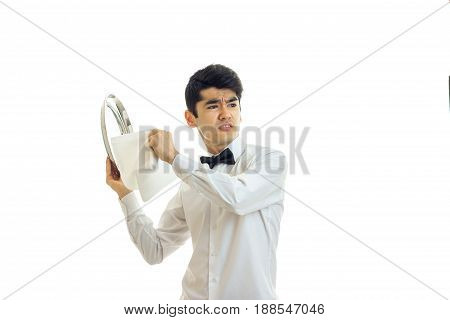 Angry young waiter cleaning silver tray and looking away isolated on white background