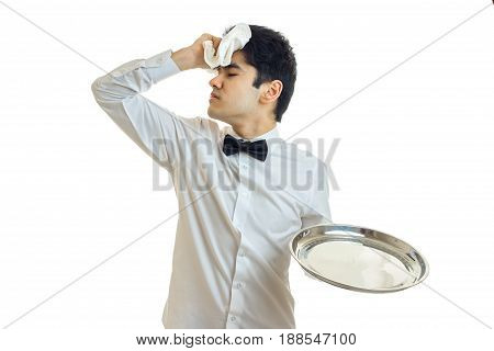 tired brunette waiter man in unifrom with silver tray in hand isolated on white background