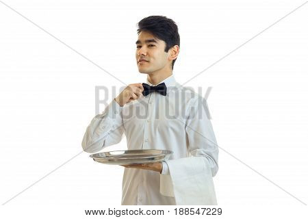 handsome man waiter in unifrom with bowtie and silver tray in his hand looking aside isolated on white background