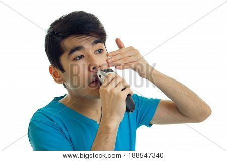 portrait of young brunette man in blue t-shirt shaving with trimmer isolated on white background