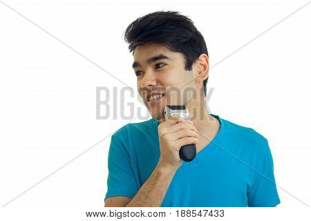 Young brunette man shaving with trimmer and smiling aside isolated on white background