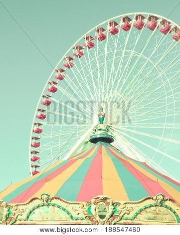 Vintage ferris wheel with colorful carousel tent
