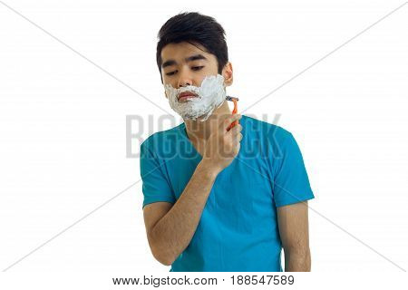 Sad young man in blue t-shirt shaving isolated on white background