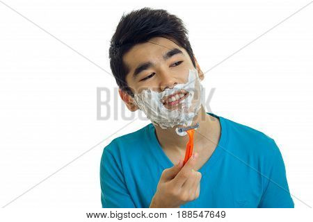 Close up portrait of young brunette man in blue t-shirt shaving and looking away isolated on white background