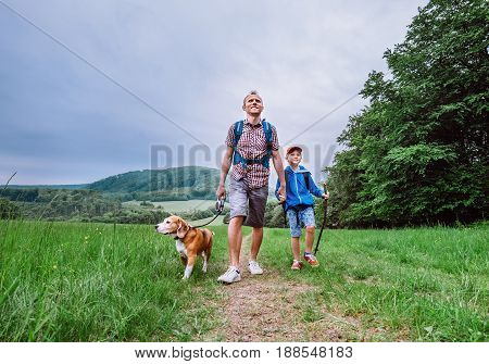 Father with son and beagle dog walk on mountain hills