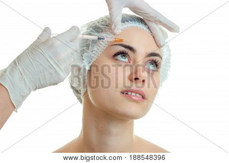 cosmetologist makes a prick on the face wrinkle girl isolated on a white background close-up