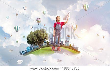 Cute kid girl on city floating island throwing paper plane