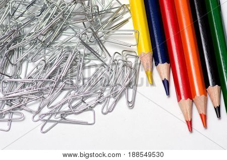 Pencils and paper clip on white background isolation