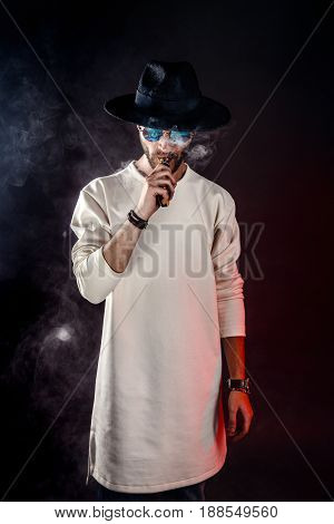 Handsome stylish man in hat and sunglasses with vapor.