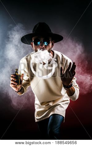 Handsome stylish man in hat and sunglasses making rings with vapor.