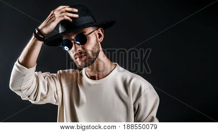 Cool stylish handsome man wearing sunglasses holding hat. Horizontal studio shot.