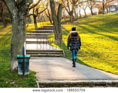 Young woman walking up the stairs in the park on cold and sunny day. Wearing warm black jacket and black beanie cap.