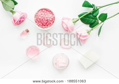 spa set with rose flowers and cosmetic for body care on white desk background top view