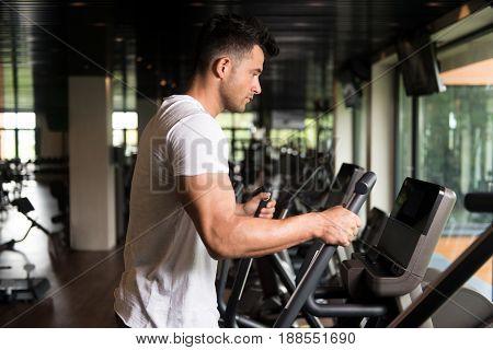 Healthy Man Doing Aerobics Elliptical Walker In Gym