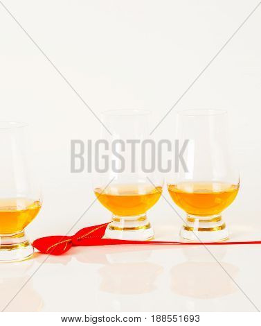 Set Of Single Malt Tasting Glasses, Single Malt Whisky In A Glasses, White Background, Red Bow
