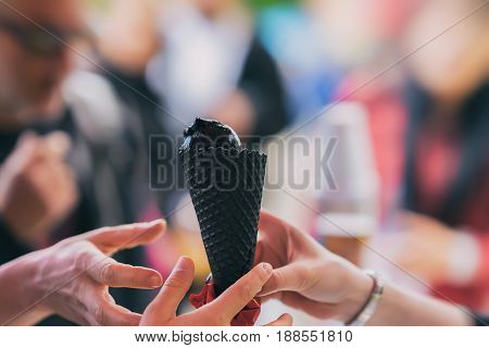 Black ice cream is the new treat of summer. Cone with black ice cream, hit a new taste, several hands are drawn to the trend. Backdrop with colorful bokeh. Copy space