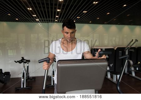 Healthy Man Doing Aerobics Elliptical Walker In Gym