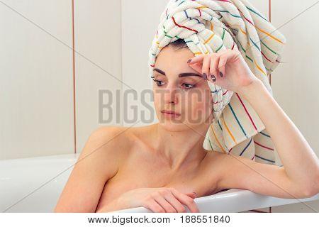 beautiful gentle girl with towel on the hair in bathtub closeup