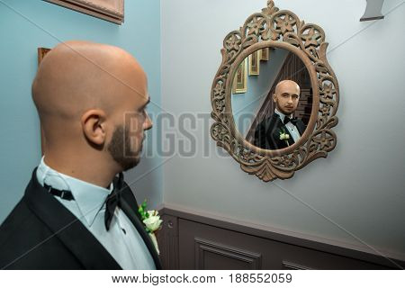 portrait of young elegant bridegroom looking at the mirror