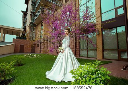 Glamour young blonde bride posing with sacura tree on background
