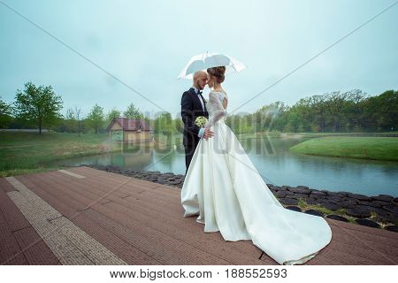 Lovely young just merried couple in wedding suits hugging under the umbrella outdoors