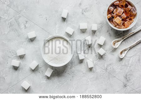 lumps of white and brown sugar on gray kitchen table background top view