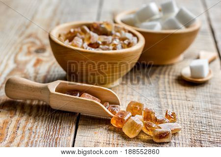 variety lumps of sugar in bowls on wooden kitchen table background
