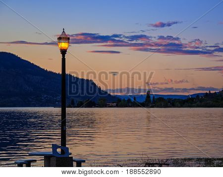 Light illuminates the shore during sunset with mountain across the water