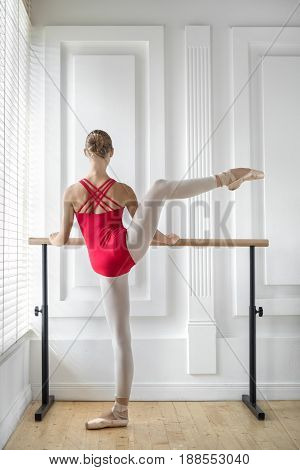 Gorgeous ballerina stands next to the ballet barre and holds her hands on it on the white wall background. She wears a red leotard and light pointe shoes. Her right leg is in the air. Indoors.