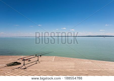 Fishing rods on wooden pier at Lake Balaton Hungary