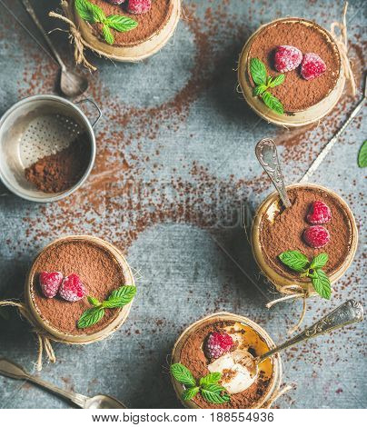 Homemade Italian dessert Tiramisu served in individual glasses with fresh mint leaves, raspberries and cocoa powder over grey concrete background, top view, copy space