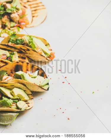 Healthy corn tortillas with grilled chicken fillet, avocado, fresh salsa, limes over light grey marble table background, copy space. Gluten-free, allergy-friendly, dieting, weight loss concept