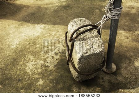 Stone tied to a iron pole on old cement ground