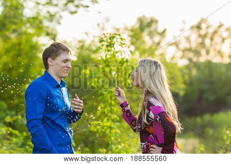 Couple in love blowing blowballs flowers in faces of each other. Smiling and laughing people having good time outside on summer warm day. Woman and man enjoying nature