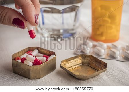 Hand Women Take Capsules Red And White In A Pillbox Metalic Old