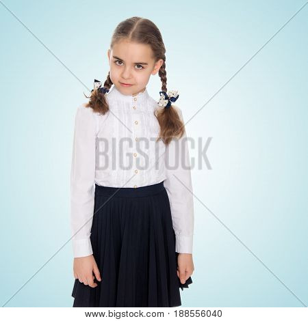 A beautiful little schoolgirl girl in a white blouse and black long skirt, with neatly braided pigtails on her head.She is standing right in front of the camera.Close-up.On the pale blue background.