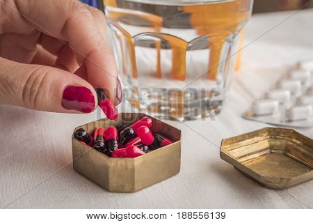 Hand Women Take Capsules Red And Black In A Pillbox Metalic Old