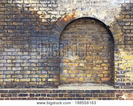 Aged brick wall with arched bricked up window wiht space for text.
