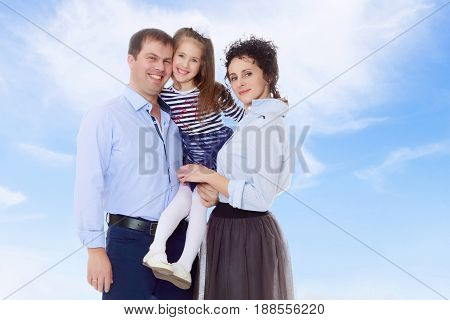 Happy young family, mom dad and little daughter.Parents keep the girl in her arms , and she hugs their neck.On the background of summer blue sky and fluffy clouds.